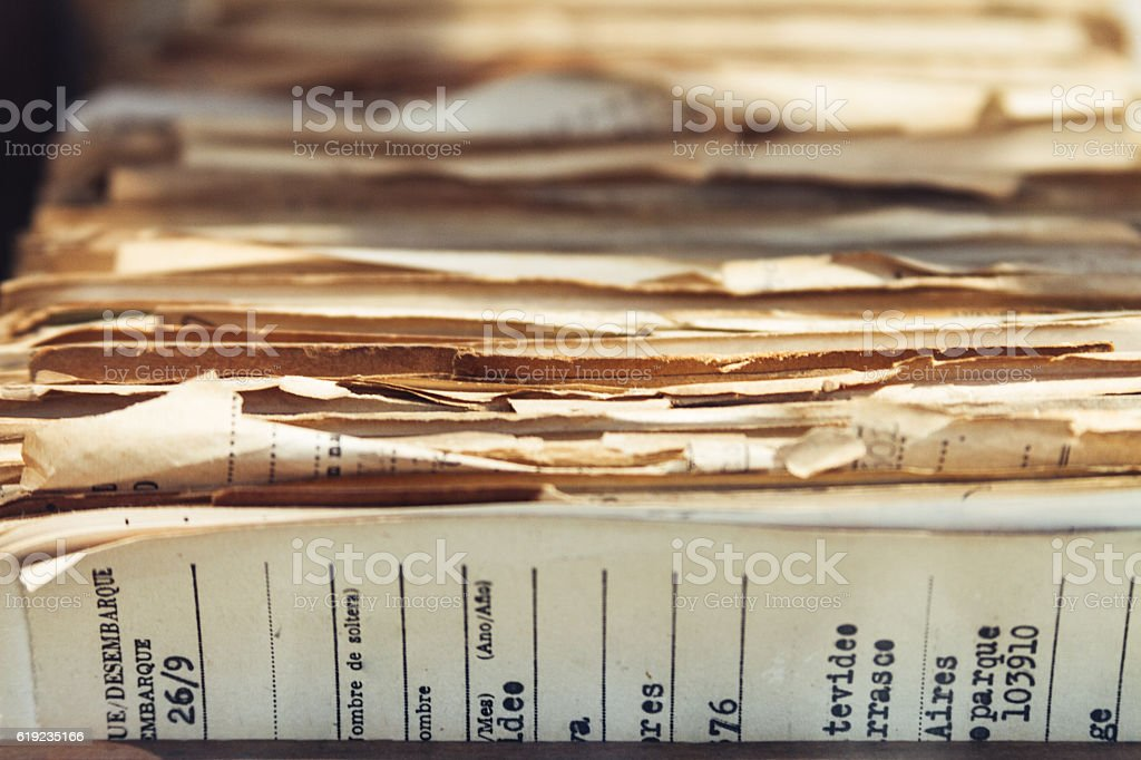 Old migrations paper records stacked in wooden box stock photo