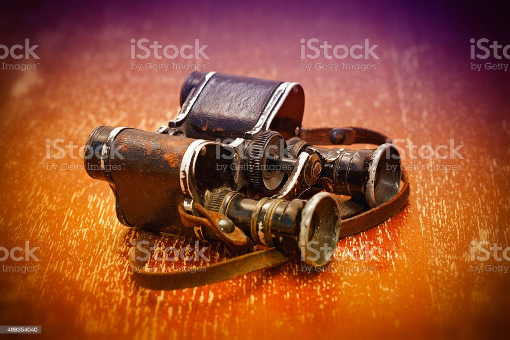 Old military binoculars on a bright orange background stock photo