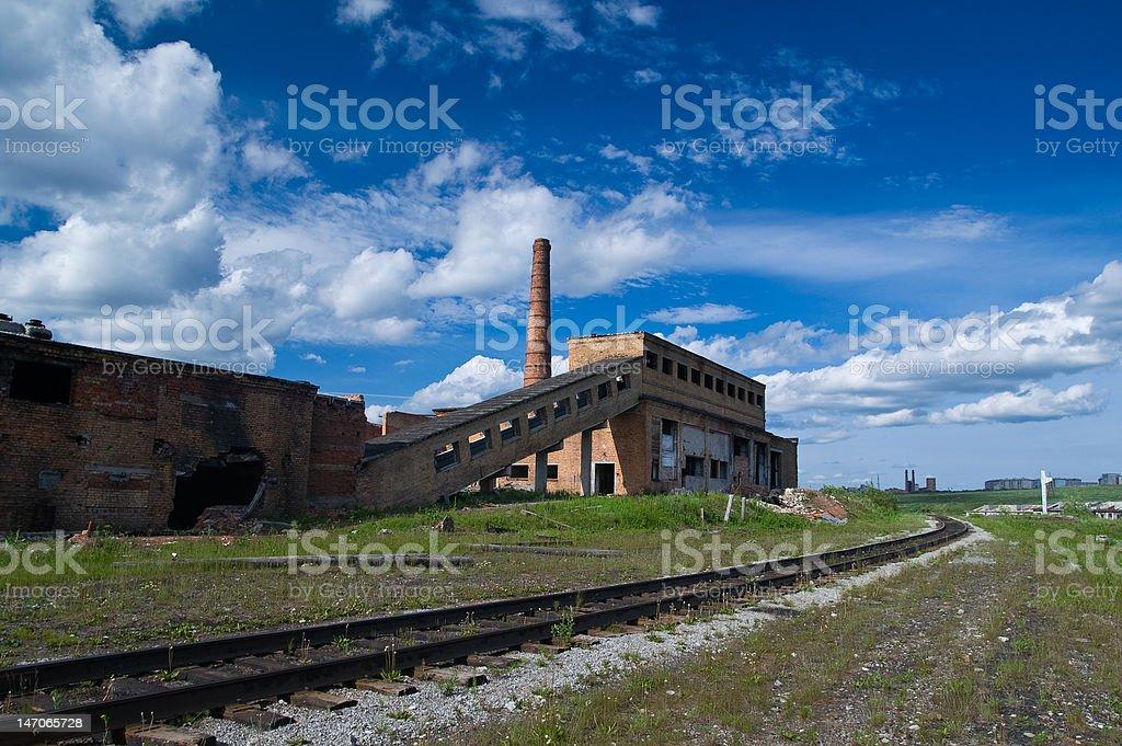 Old mine ruins near rusty rails under the wonderful sky royalty-free stock photo