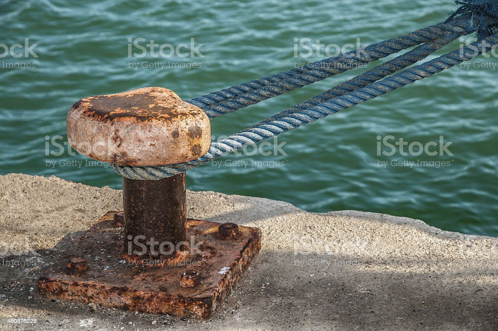 Old mooring post with a blue rope on harbor stock photo