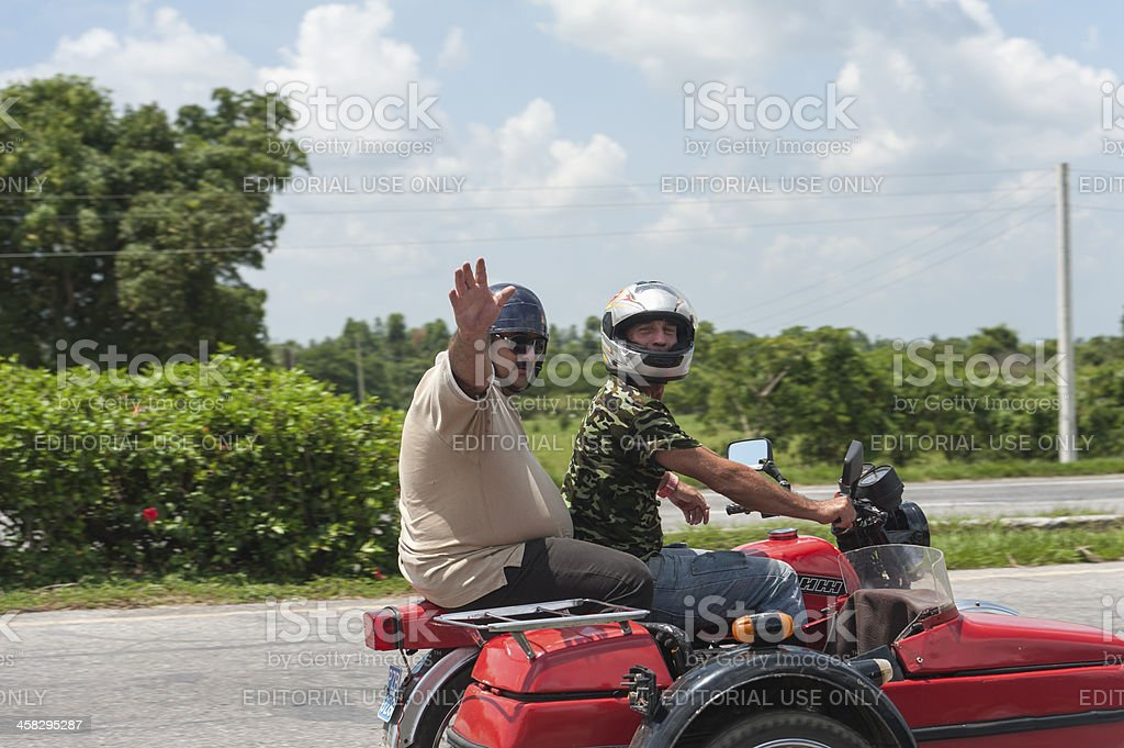 old motor with two men looking and waving, Cuba royalty-free stock photo