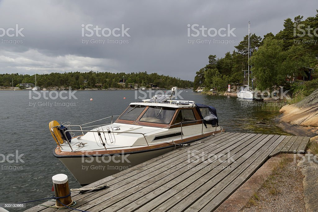 Old motorboat by bridge in Stockholm Archipelago under cloudy sky. stock photo