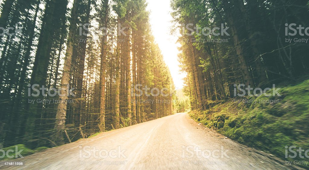 Old mountain road leading to a bright light stock photo