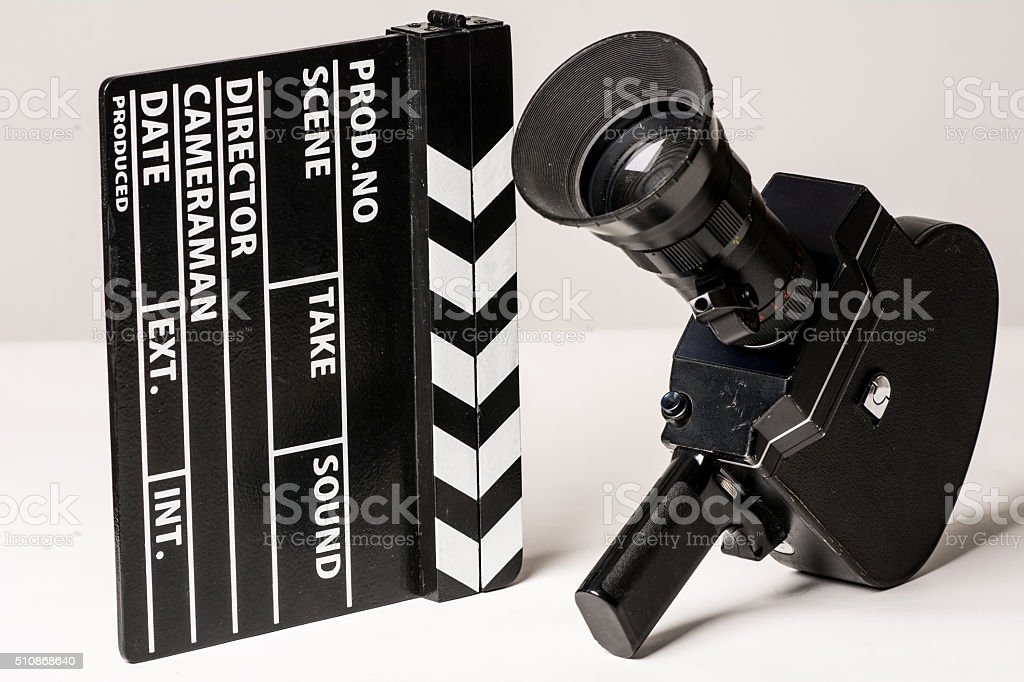 Old movie camera with film clapperboard. stock photo