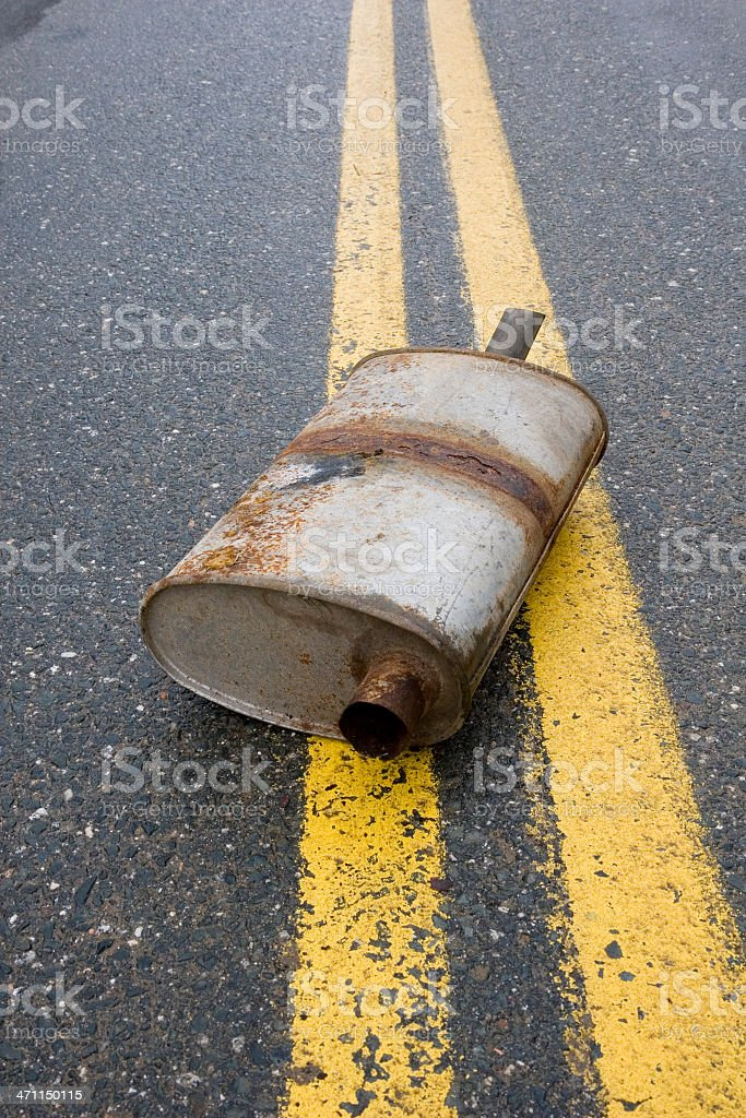 Old muffler in the road royalty-free stock photo