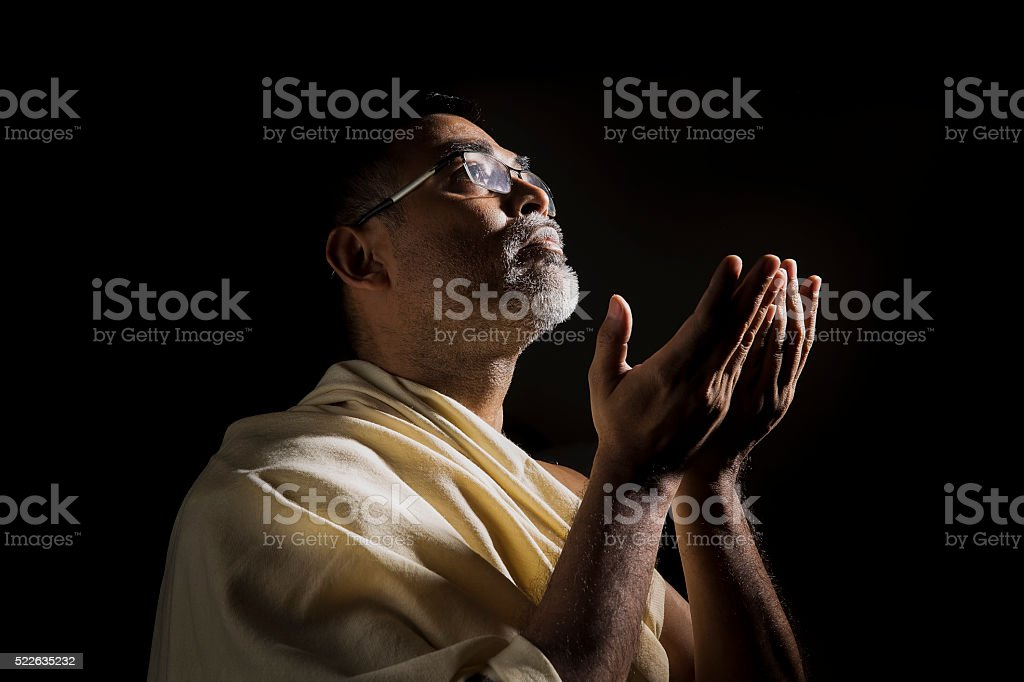 Old Muslim man praying with folded hands stock photo