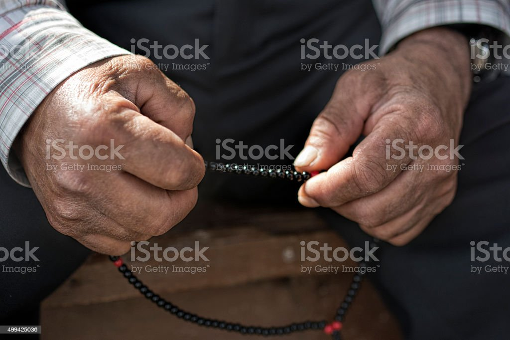 Old muslim Man with rosary praying stock photo