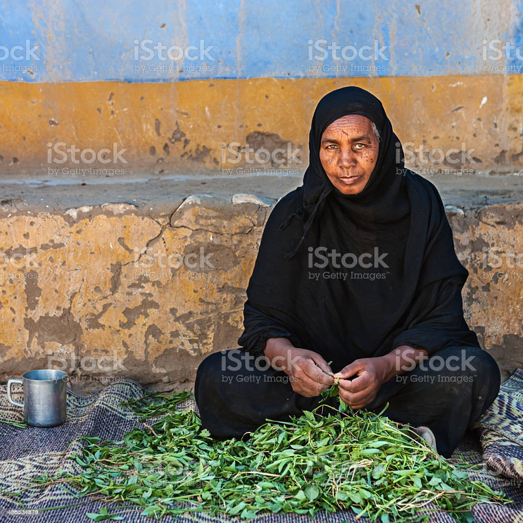 Old Muslim woman sorting spinach in Southern Egypt stock photo