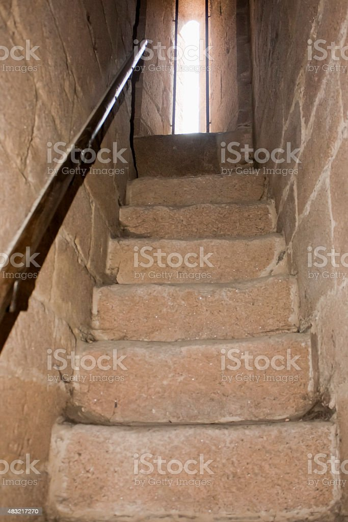 Old narrow granite stone staircase, handrail. stock photo