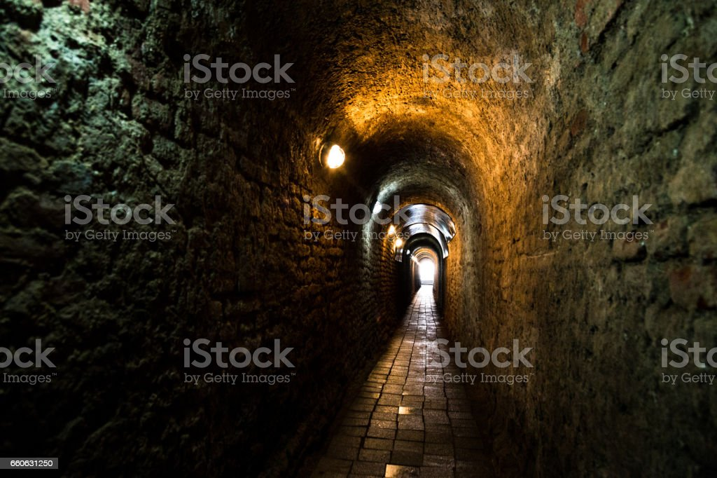 Old narrow spooky illuminated tunnel in Alba Iulia, Romania stock photo