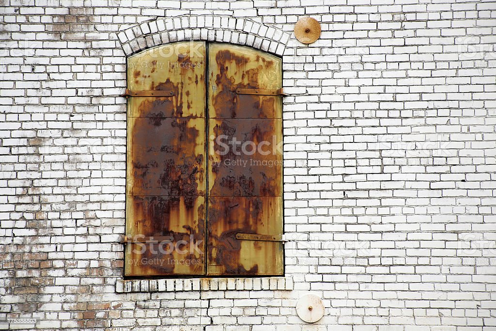 Old neglected rusty shutters closed on aging brick building royalty-free stock photo