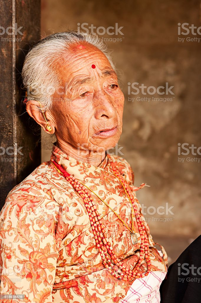 Old Nepali woman resting in Bhaktapur stock photo