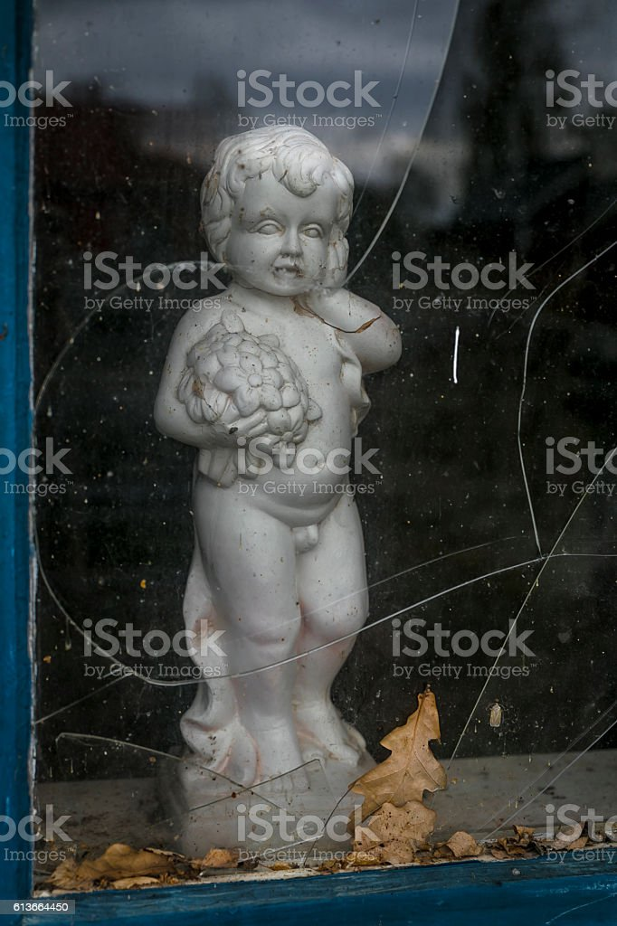 Old no name figurine looking out from a autumn window stock photo