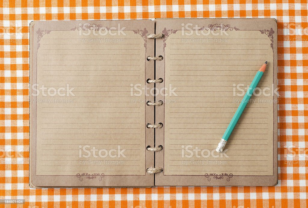 Old notebook and pencil on orange tableclot royalty-free stock photo