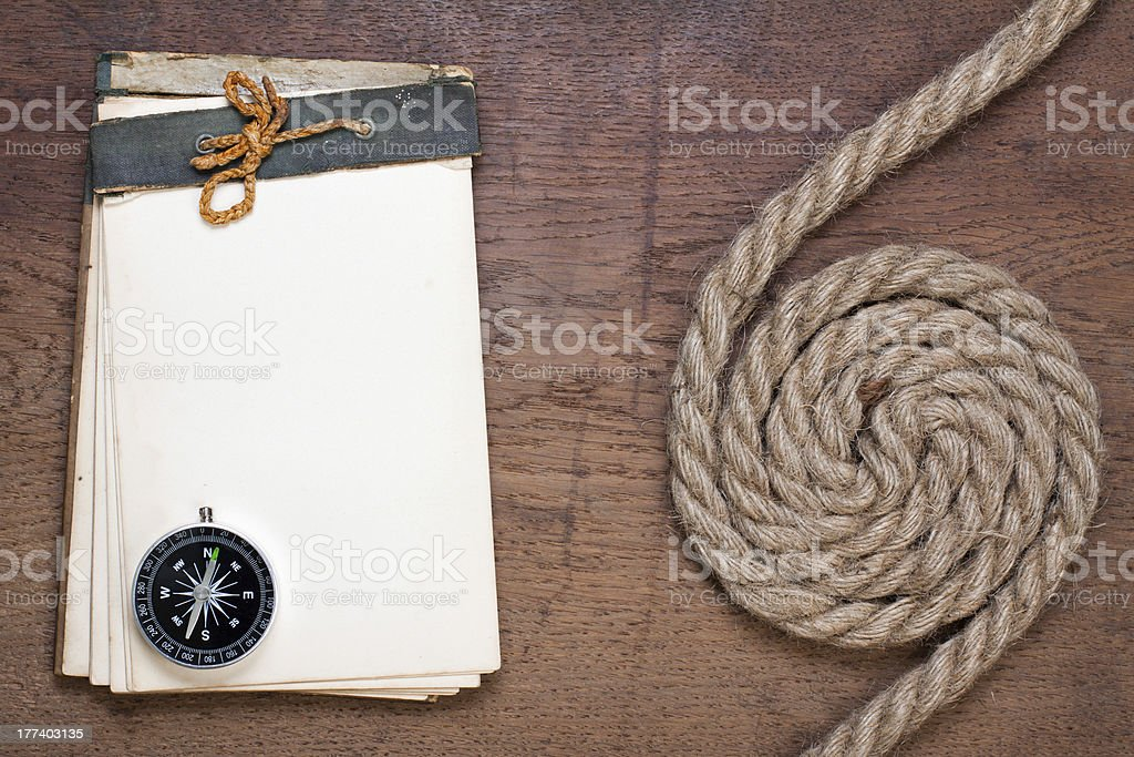 Old notebook, compass, rope on wood texture royalty-free stock photo