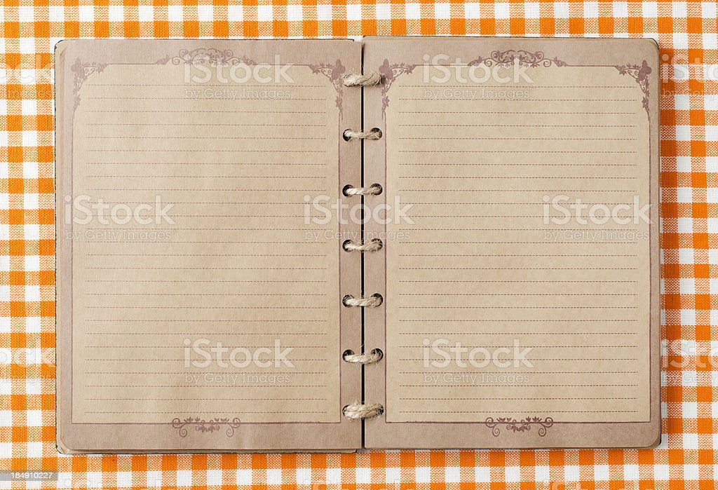 Old notebook on orange tableclot stock photo