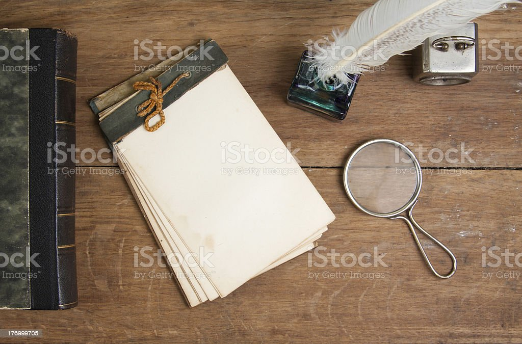 Old notepad, book, quill and inkwell, magnifying glass on wood royalty-free stock photo