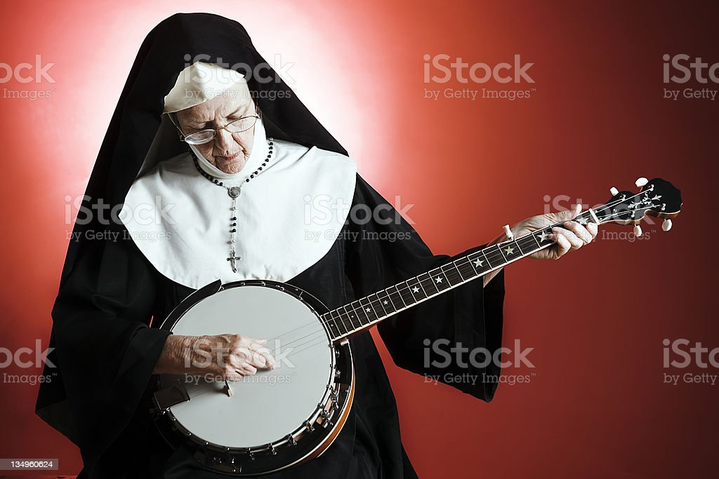 Old nun picks out a tune on banjo stock photo