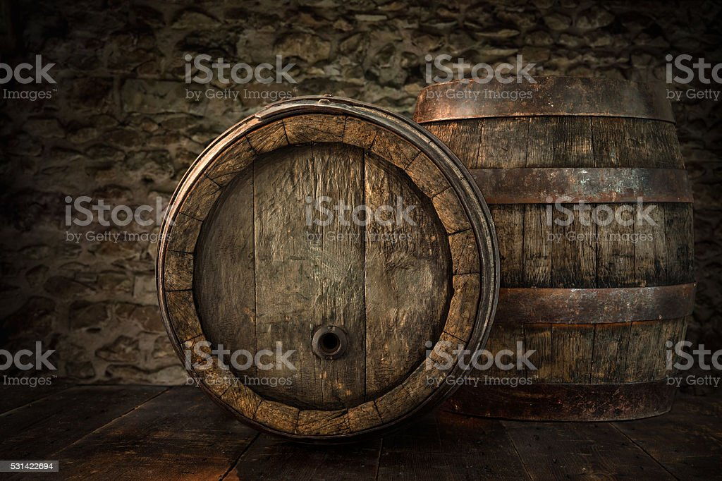 Old oak barrels on blurred cellar wall stock photo