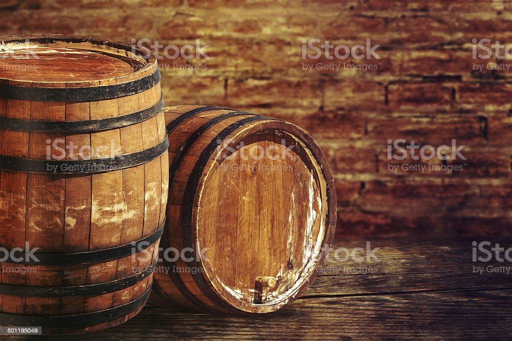 Old oak barrels on the brick wall backgroung. stock photo