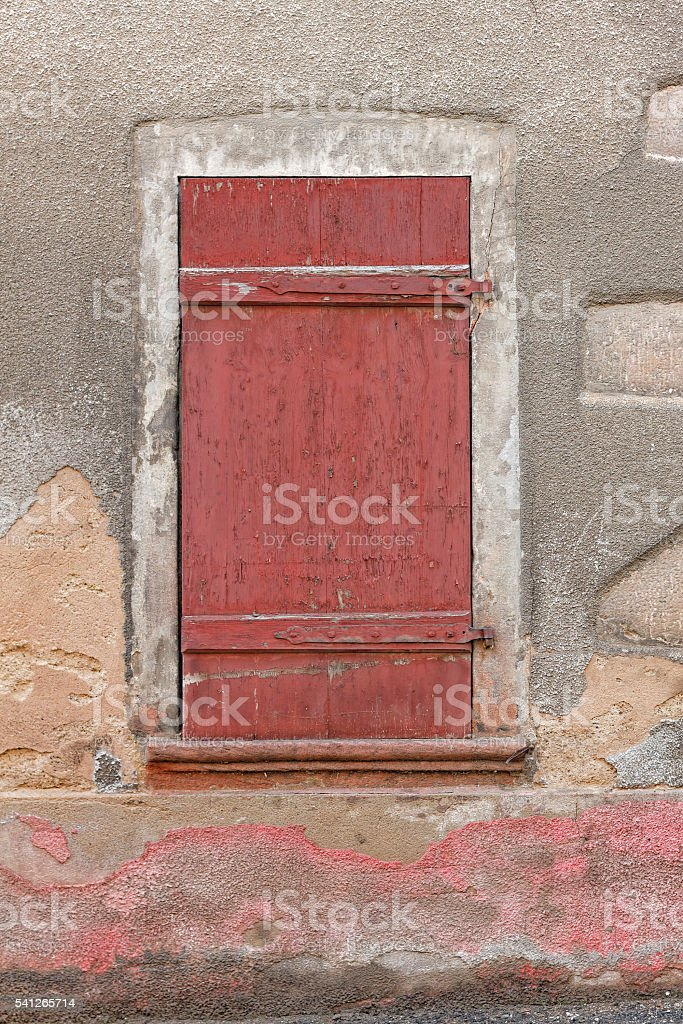 Old obsolete house and window with red wooden shutter stock photo