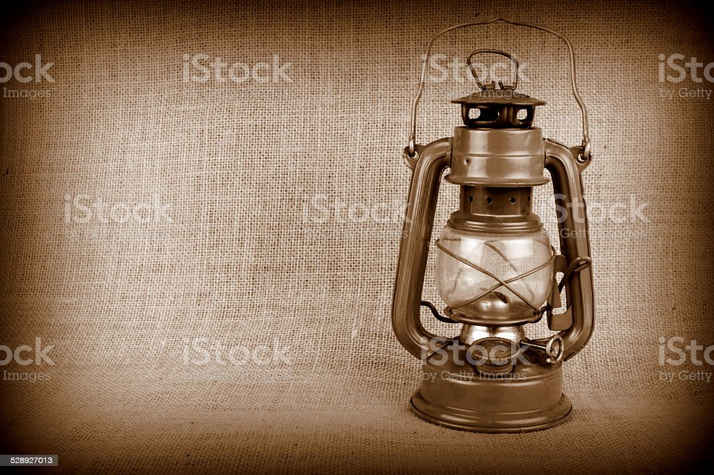 Old oil lamp on burlap and copy space stock photo