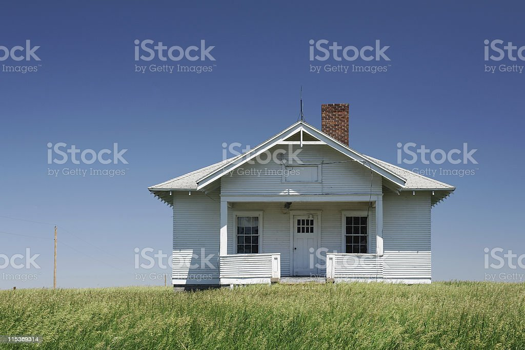 Old one room school house on a grassy open plain royalty-free stock photo