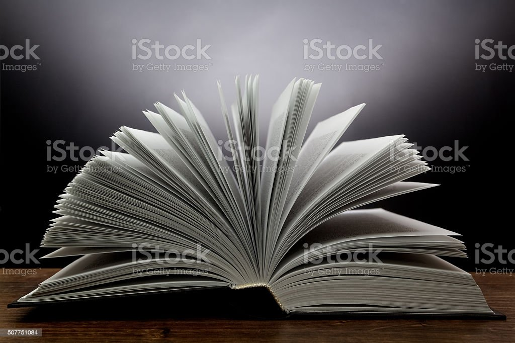 Old open book with light on a dark background stock photo
