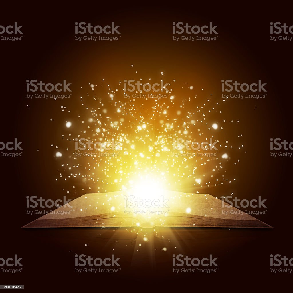 Old open book with magic light and falling stars stock photo
