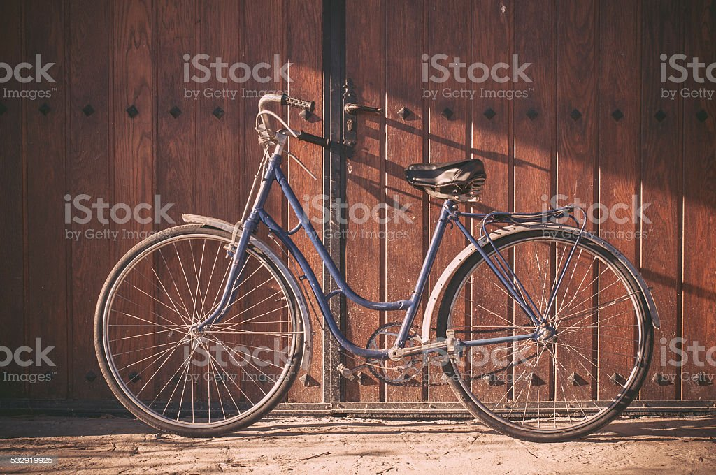 Old or classic bicycle on a wooden door stock photo