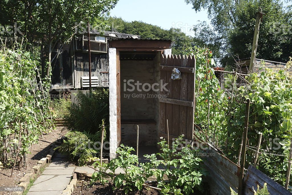 old outhouse or outside toilet in the vegetable garden royalty-free stock photo