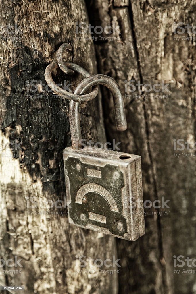 Old padlock hanging on the rotting jamb stock photo