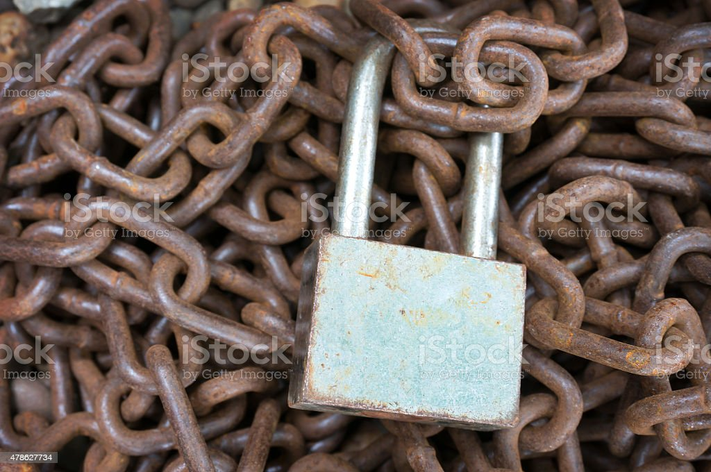 Old padlock on a pile of rusty chains stock photo