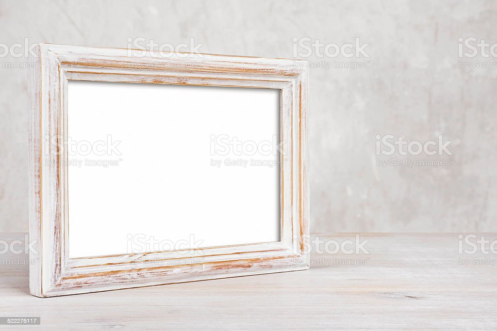 Old painted photo frame on table over abstract background stock photo