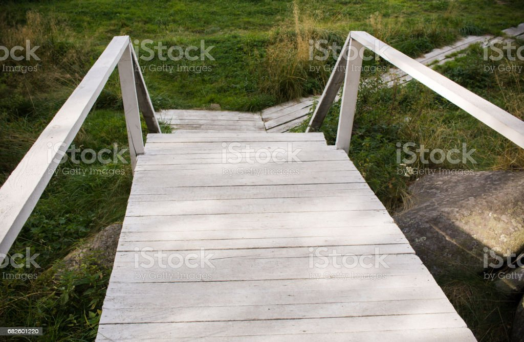 Old painted white paint the bridge and wooden path amongst the green grass. stock photo