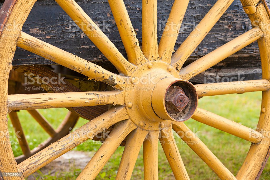 Old painted yellow wagon wheel on historic cart stock photo