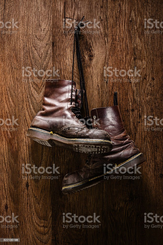 Old pair of brown boots hanging on a wall stock photo