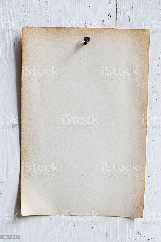Old paper nailed to a weathered wooden board. stock photo