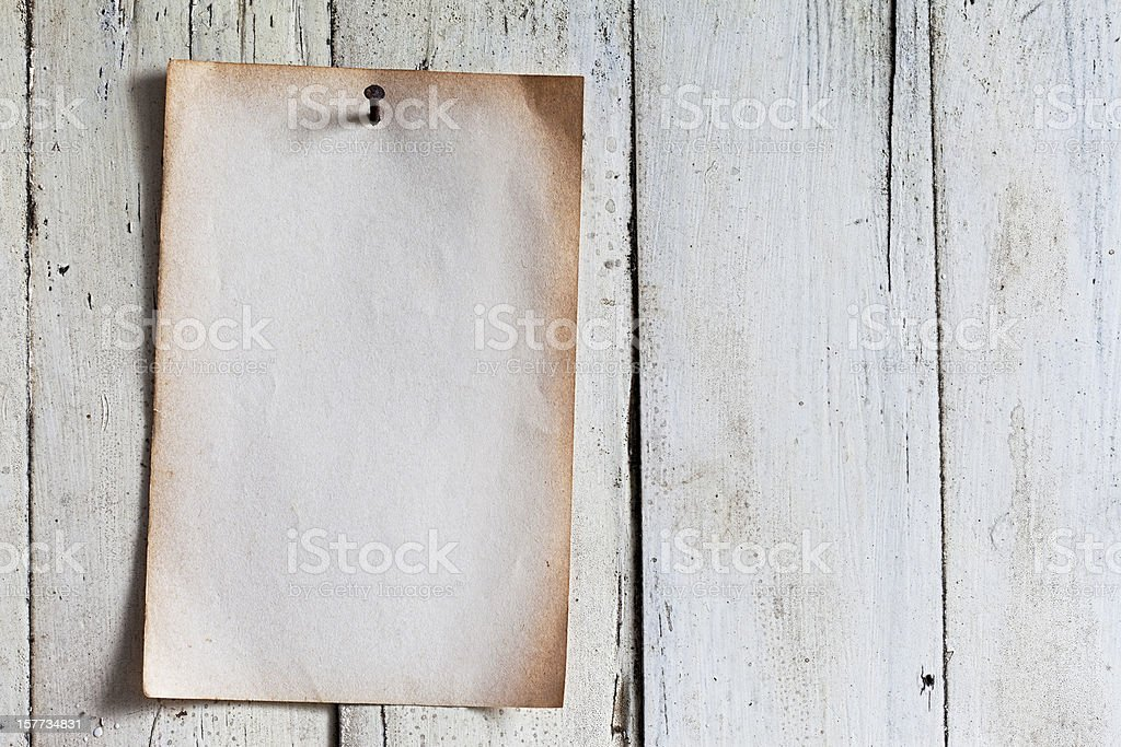 Old paper nailed to a weathered wooden board. royalty-free stock photo