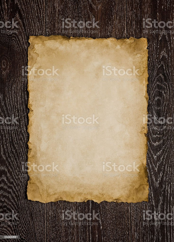 Old paper sheet on brown wooden background stock photo