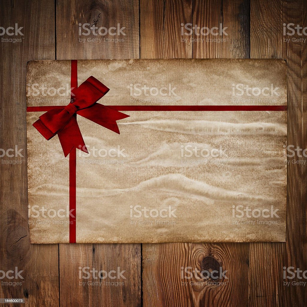 Old paper  with red ribbon on  wooden wall royalty-free stock photo