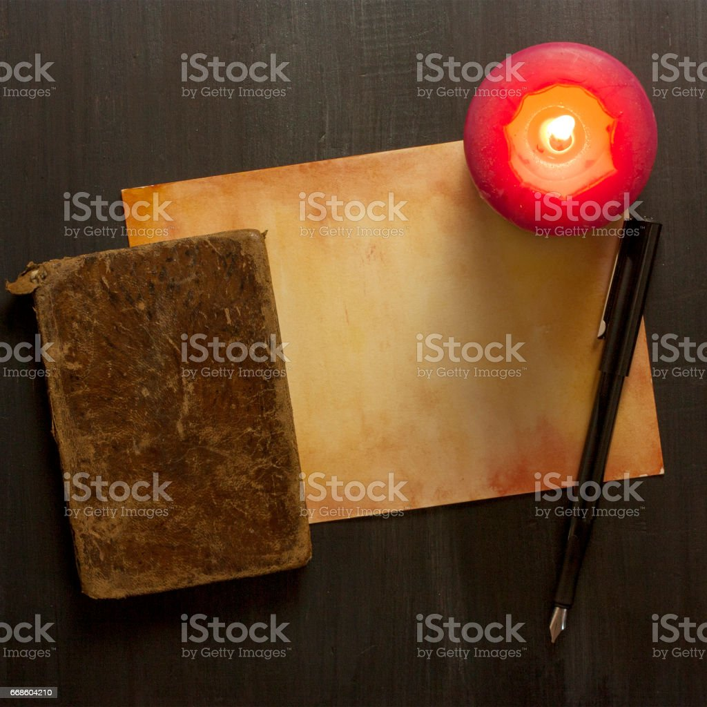 Old parchment, burning candle, vintage book, and nib pen stock photo