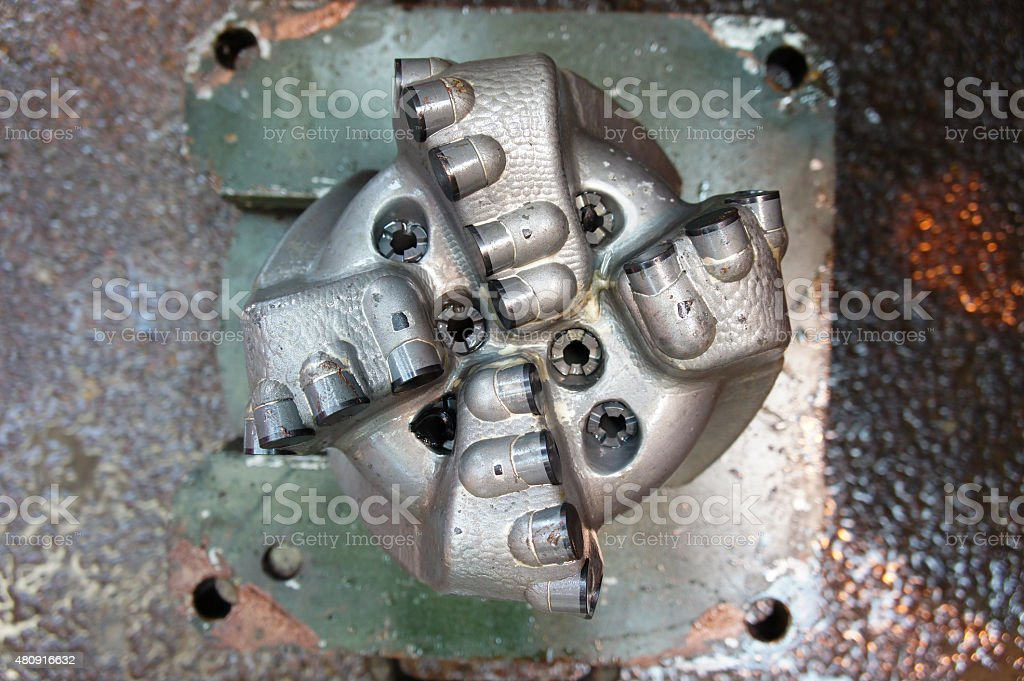 Old PDC drilling bit just pulled out of hole stock photo