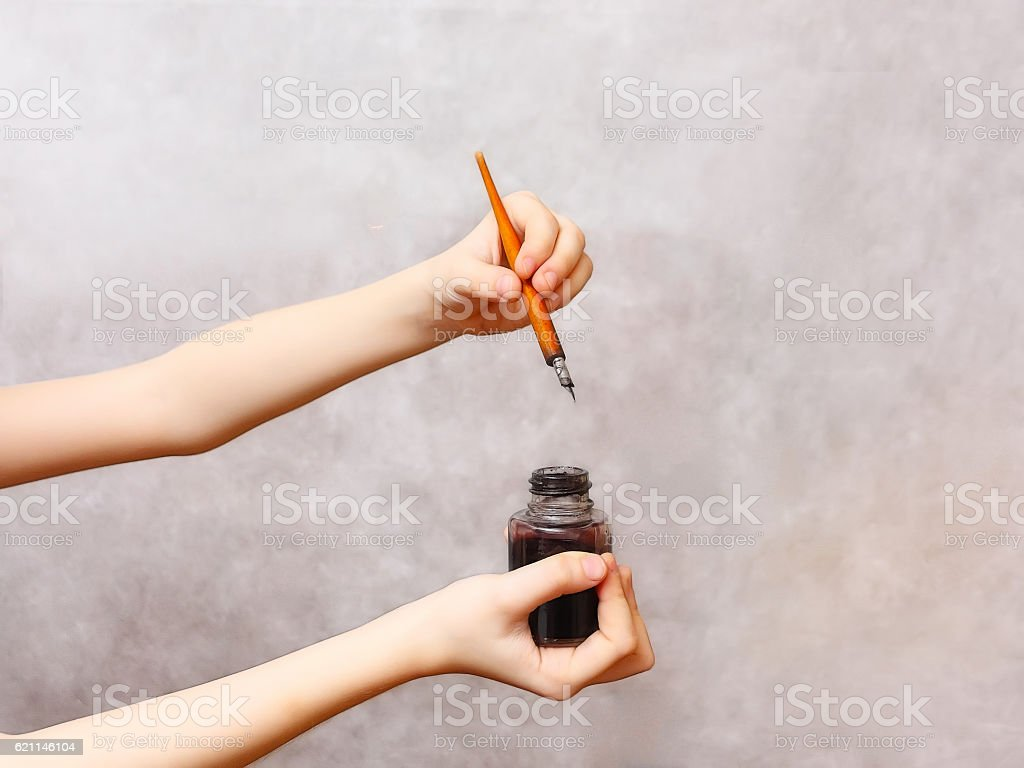 Old pen and ink in hand stock photo