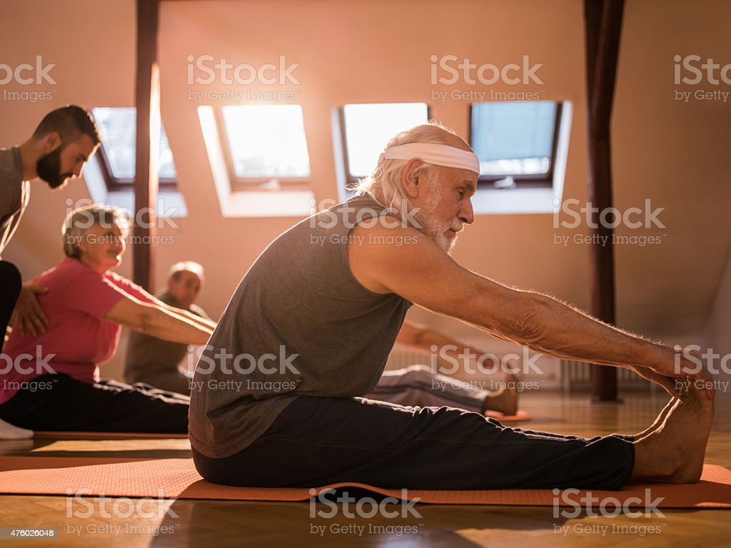 Old people doing stretching exercises in a health club. stock photo