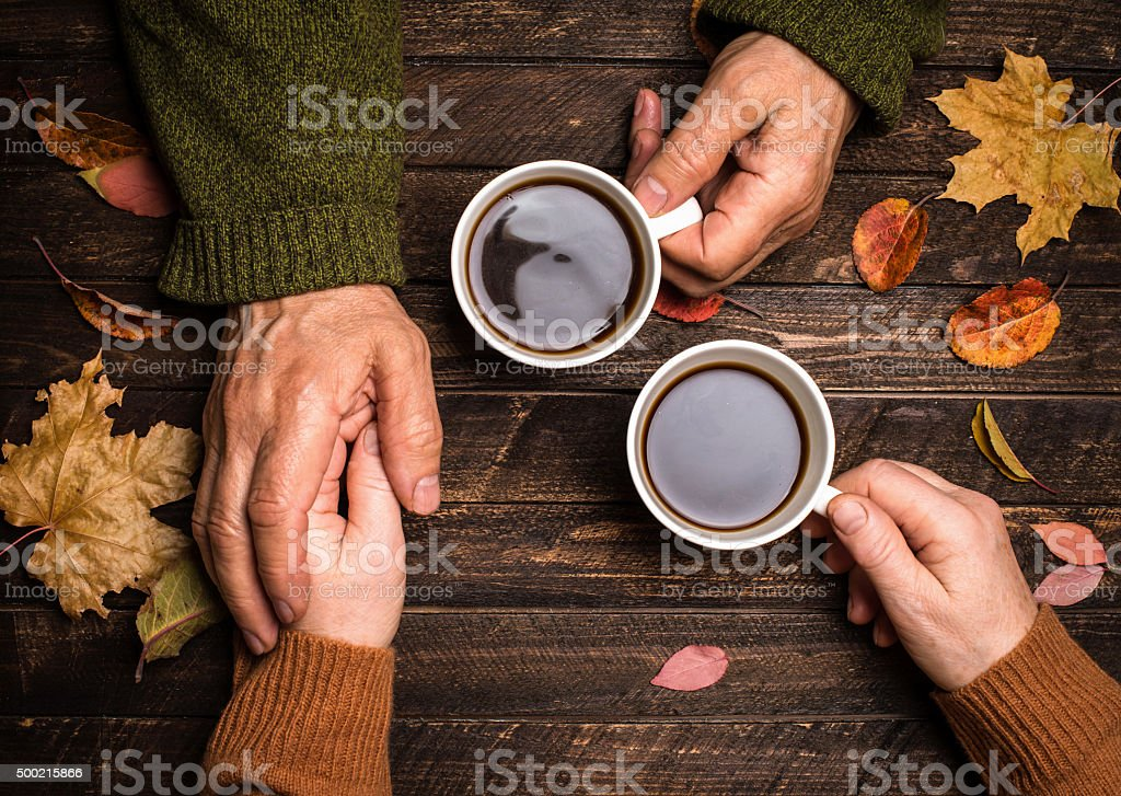 Old people holding hands. Senior people hand holding coffee cup. stock photo