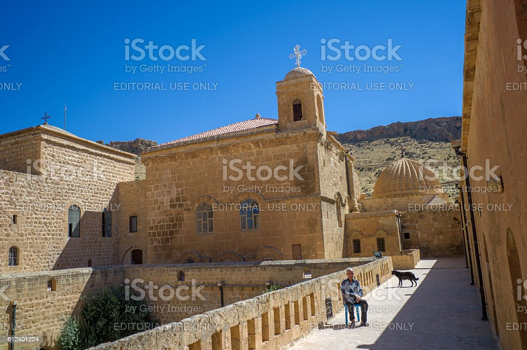 old person sitting  at Deyr ul-Zafaran Monastery in mardin turkey stock photo