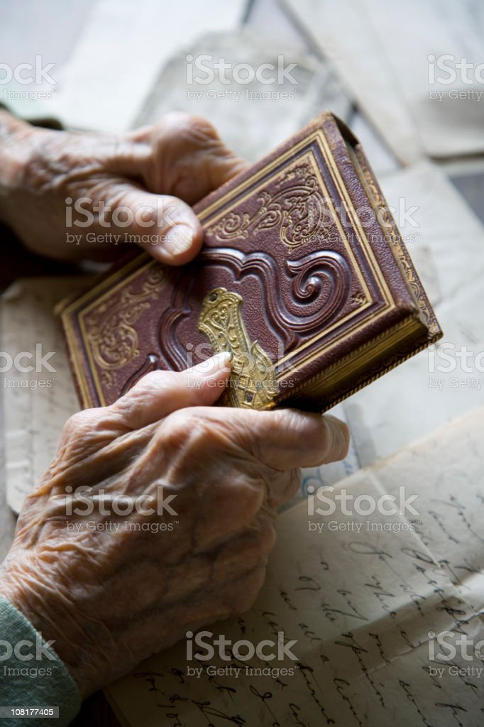 Old Person's Hands Holding Antique Book and Lettters royalty-free stock photo