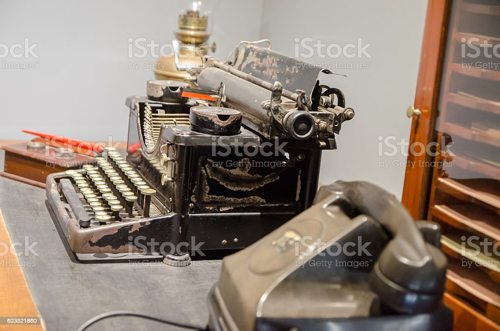 Old phone, typewriter, ink pen and oil lamp on table stock photo
