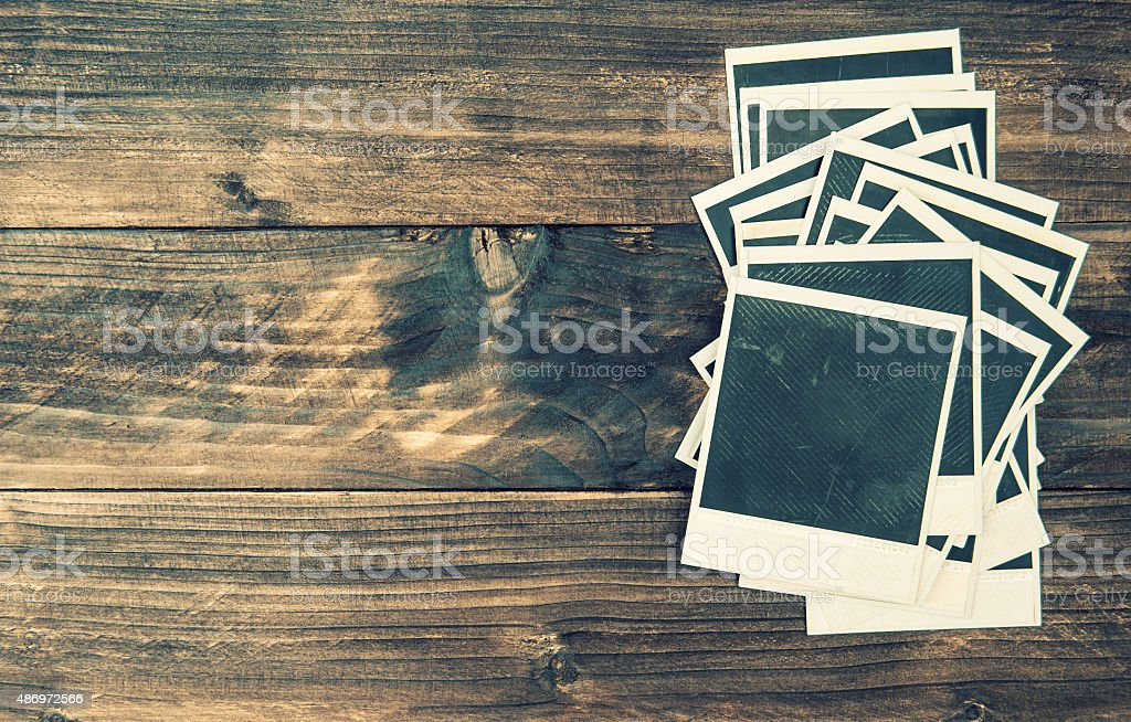 Old photo frames on rustic wooden background Vintage style stock photo